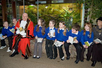 The Lord Mayor and Lady Mayoress of Bristol reading the books in the reptile house of Bristol Zoo Gardens with pupils from New Oak Primary.